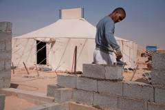Un jeune Sahraoui construit sa maison en béton devant la tente de sa mère.