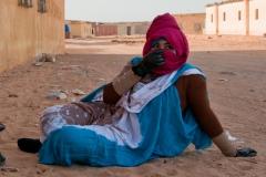 Une femme dans le camp de Boujdour. Les femmes se protègent le corps du soleil pour ne pas bronzer. Elles portent des vêtements chauds, car il est communément admis que la transpiration facilite le blanchissement de la peau. Une peau claire est un critère de beauté pour les Sahraouis.